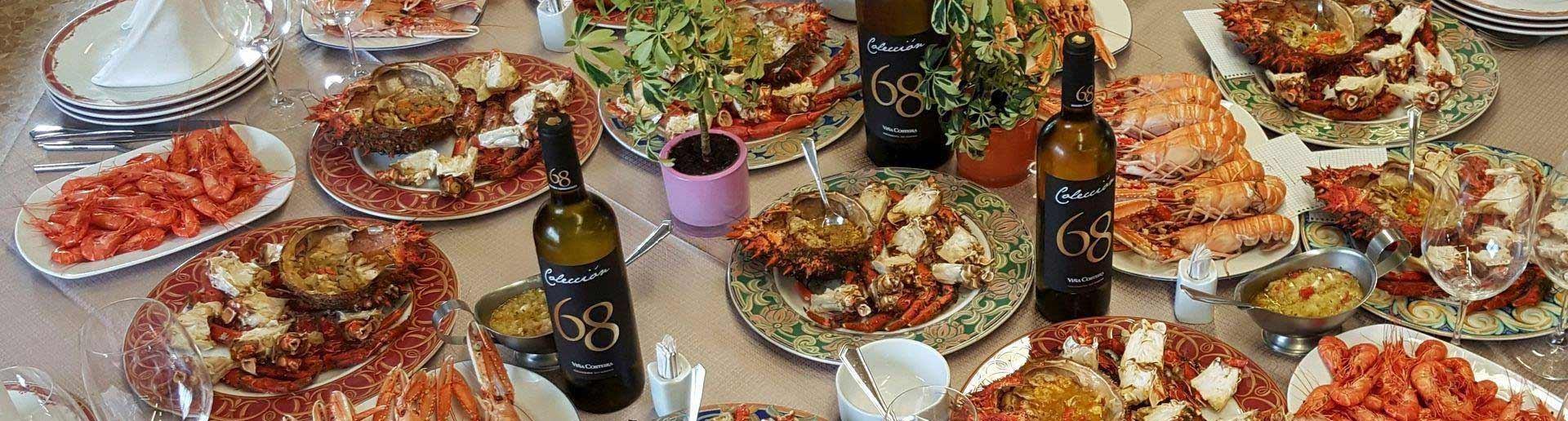 Mesa con surtido de mariscos y vino blanco: camarones de la ría, centolla fresca gallega, cigalas de la ría, nécoras frescas