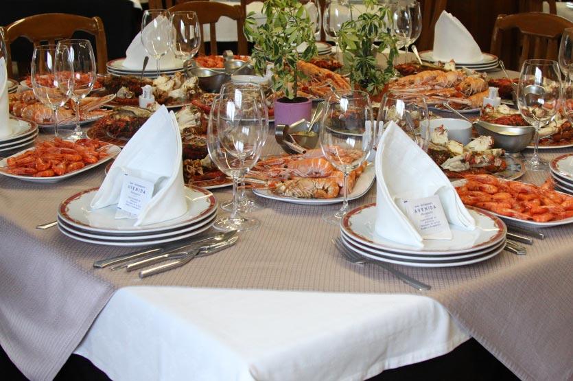 Mesa de restaurante con platos llenos de mariscos frescos de las rías gallegas: cigala fresca, camarón de la ría, nécora gallega, y centolla de la ría